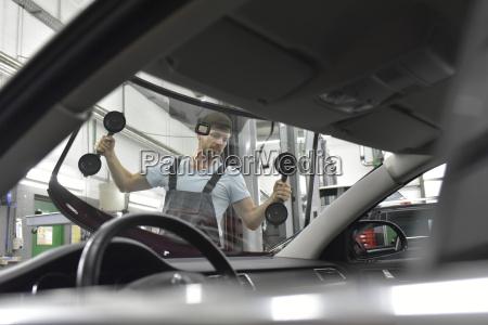 automechaniker in einem aendernden autofenster der