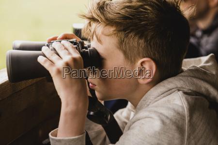 boy birdwatching mit fernglas