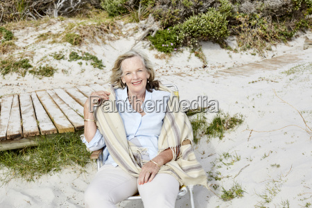 AEltere frau die auf dem strand