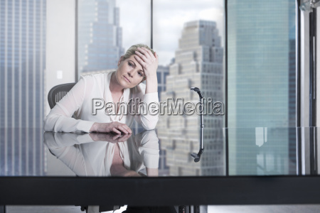 serious businesswoman sitting at desk in