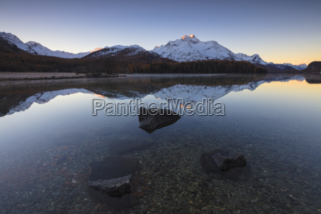 the snowy peaks are reflected in