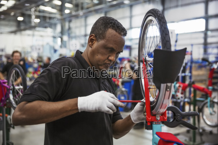 male skilled factory worker assembling a