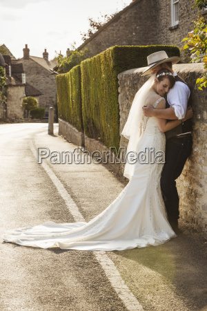 newlyweds standing outdoors on a pavement