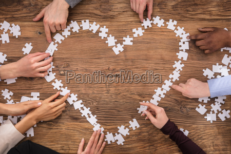 businesspeople forming heart shape with jigsaw