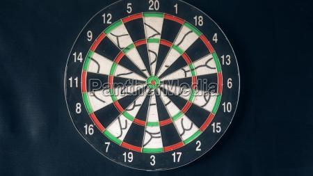 sechs dart arrows hitting in dartboard