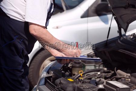car or motor mechanic checking a