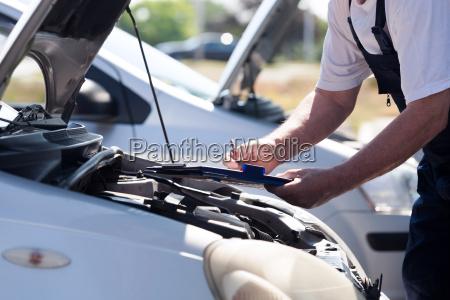 auto mechanic checking car engine and