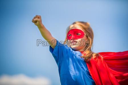 lustige kleine maedchen spielen macht superheld
