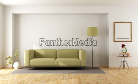 white room with green sofa