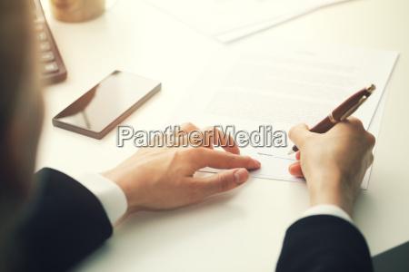 businesswoman putting signature on business partnership