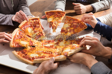 group of businesspeople eating pizza