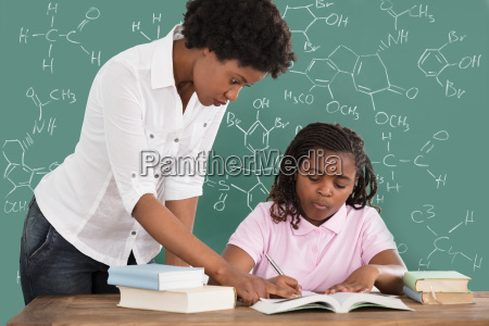 female teacher assisting student in class