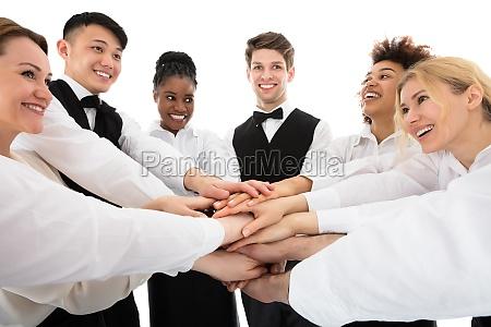 laechelnde junge restaurant personal stacking hands