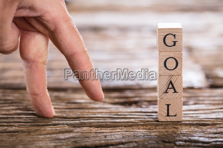 persons finger and goal text on