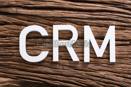 white crm text on wooden table