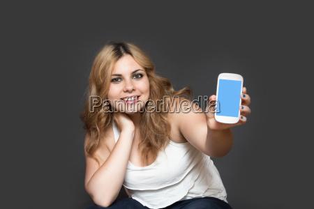 laechelnde teenager maedchen zeigt ihr smartphone
