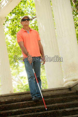 blind man walking and descending stairs