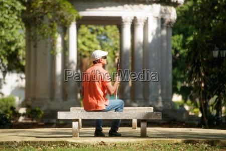 blind man sitting in city park