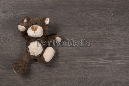 brown teddy bear on wooden background