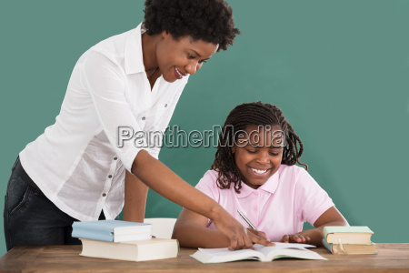 happy teacher teaching her student