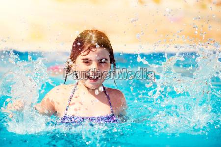 glueckliches kleines maedchen im pool