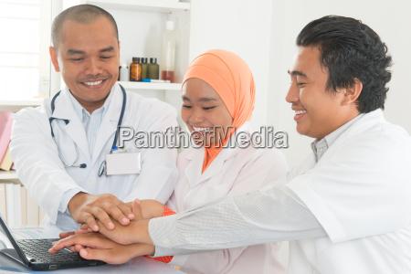 medical doctors stacking hands