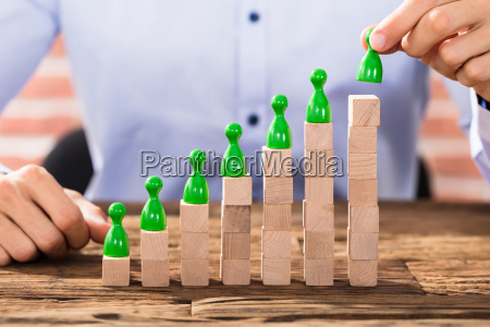 businessman arranging the figures on block