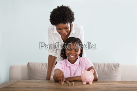 girl with mother inserting coins in
