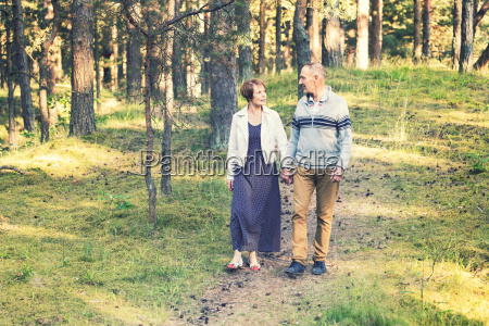 senior couple walking on forest trail