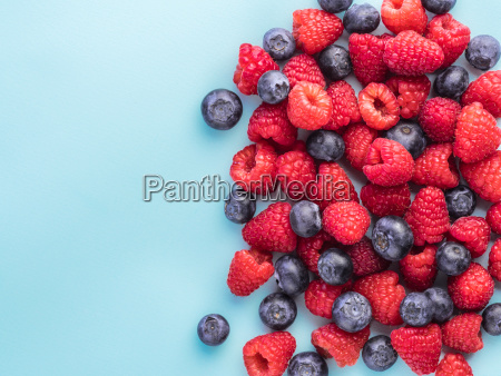 raspberry and blueberry on blue background