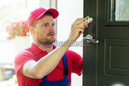 handyman fixing house door lock