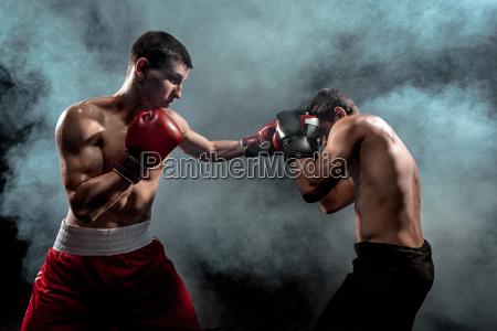 zwei professionelle boxer boxen auf schwarzem