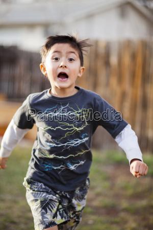 japanese american boy running in backyard
