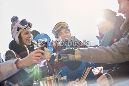 skifahrer freunde toasten cocktailglaeser apres ski