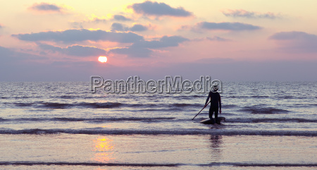 silhouette of male stand up paddle