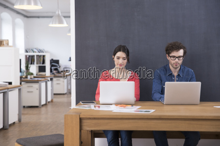 man and woman using laptops on
