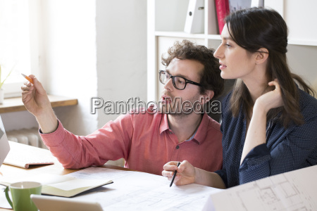 man and woman discussing at desk