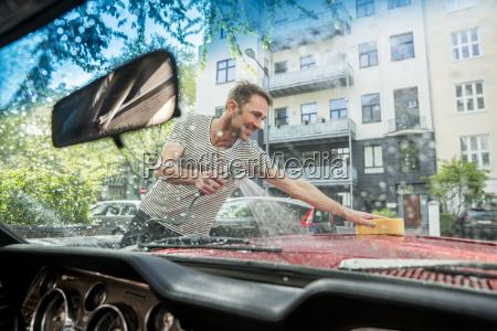 laechelnder reifer mann der sein auto