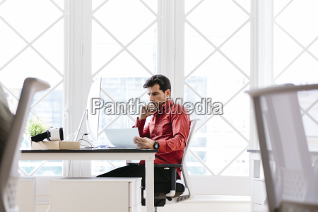 businessman working in office reading papers