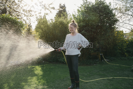 young woman sprinkling lawn in the
