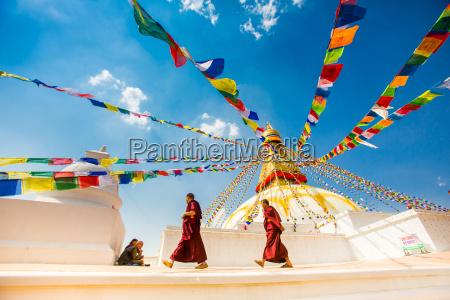 buddhist monks walking around stupa at