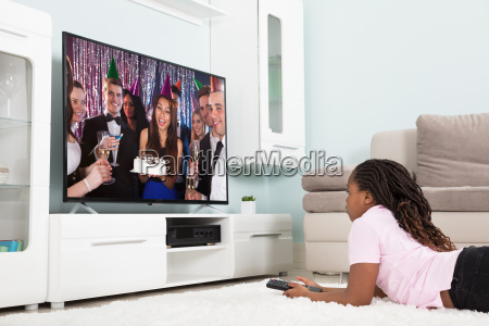 girl watching television at home