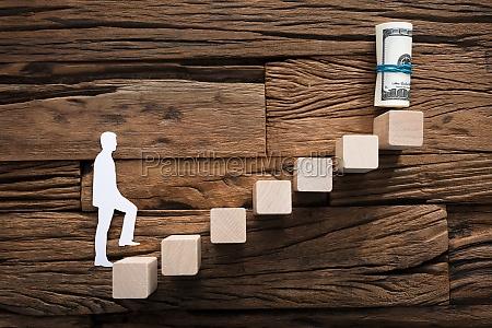paper businessman climbing ladder leading towards