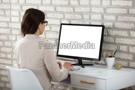 businesswoman using computer with blank screen