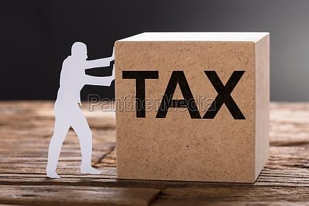 paper man pushing tax wooden block