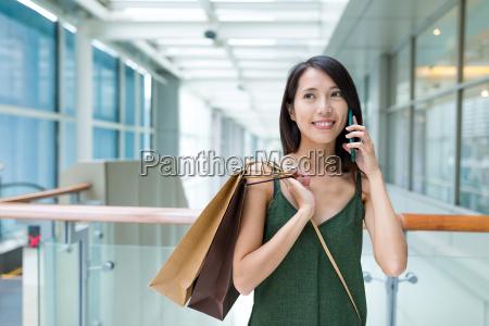 frau einkaufen gehen und mit handy