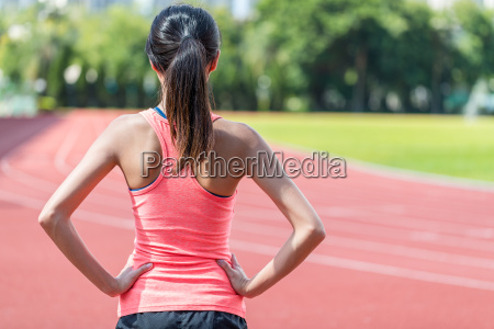 rueckansicht der sportfrau im laufenden stadion