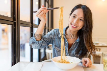 asian woman eating noodles in chinese