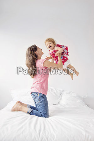 woman kneeling on bed throwing young