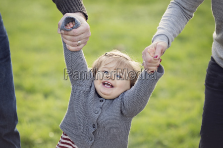 young girl holding hands of man